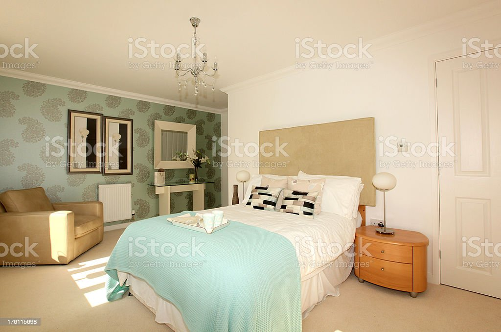 Modern and contemporary brightly lit bedroom with double bed royalty-free stock photo