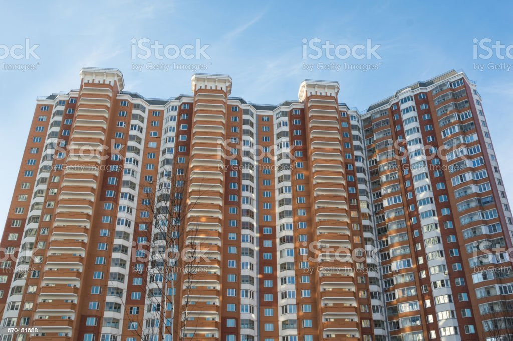 Modern and new apartment building. Photo of a tall block of flats against a blue sky. stock photo