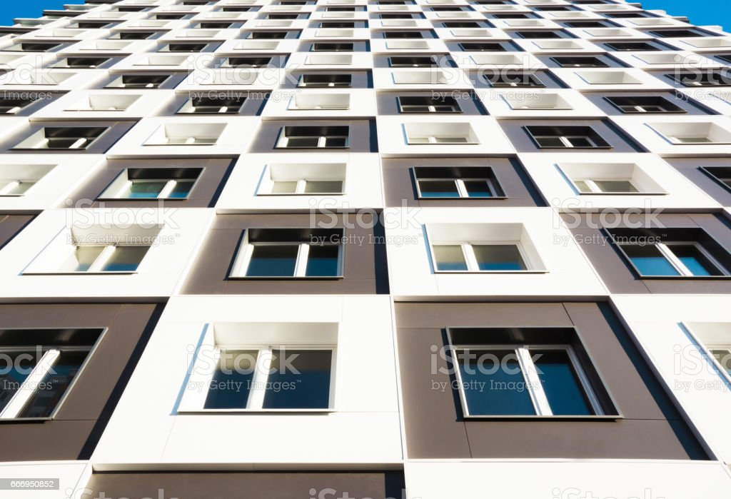 Modern and new apartment building. Photo of a tall block of flats with balconies in Moscow against a blue sky. stock photo