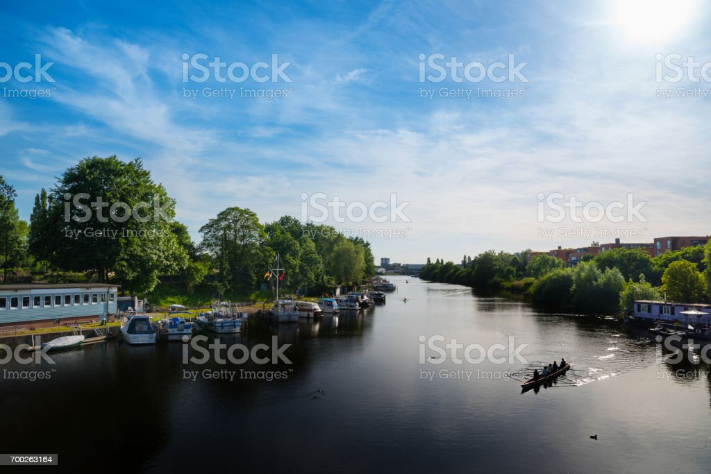 modern apartment buildings and boats on a river in Hamburg, Germany under blue summer sky stock photo