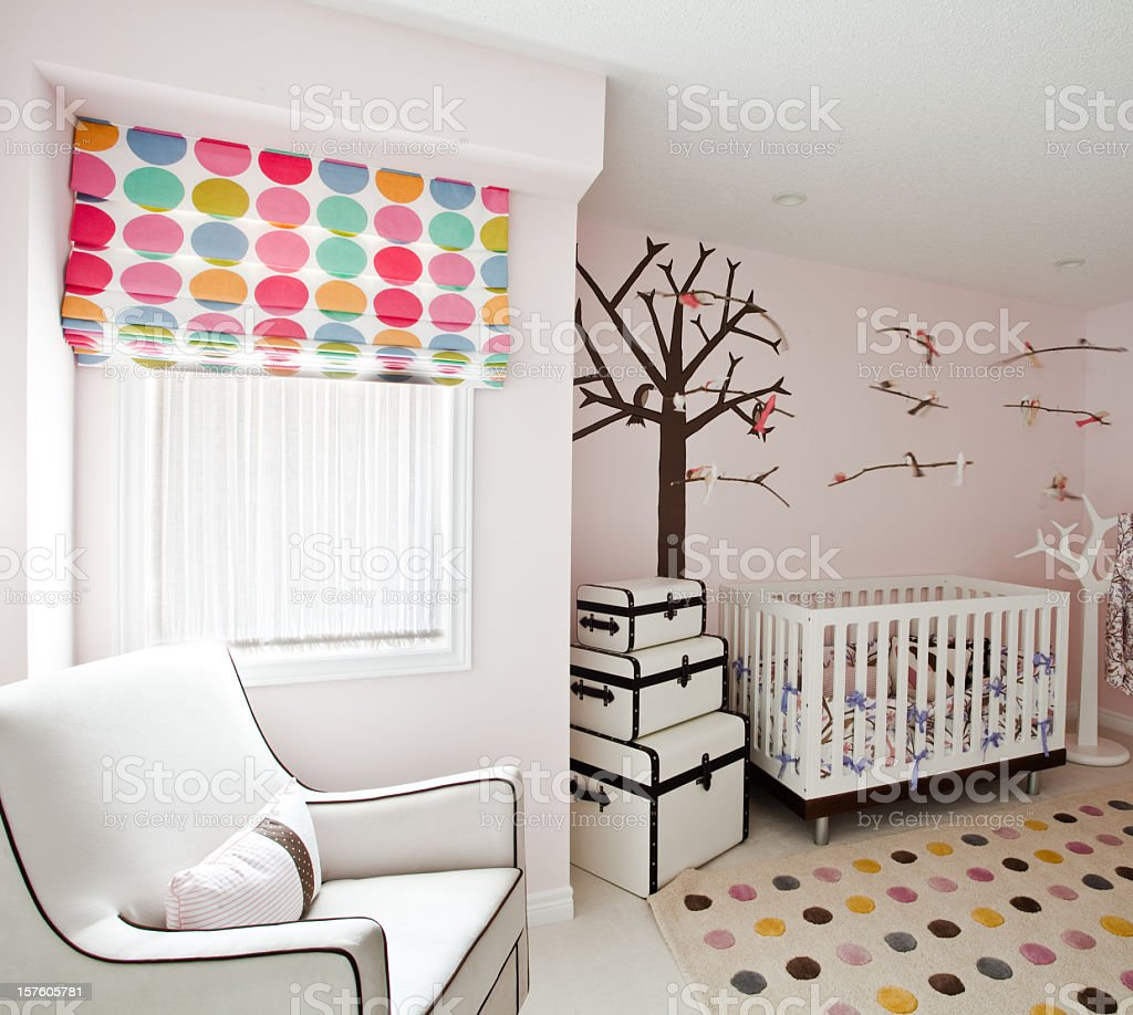 Modern baby nursery with polka dots and trees stock photo