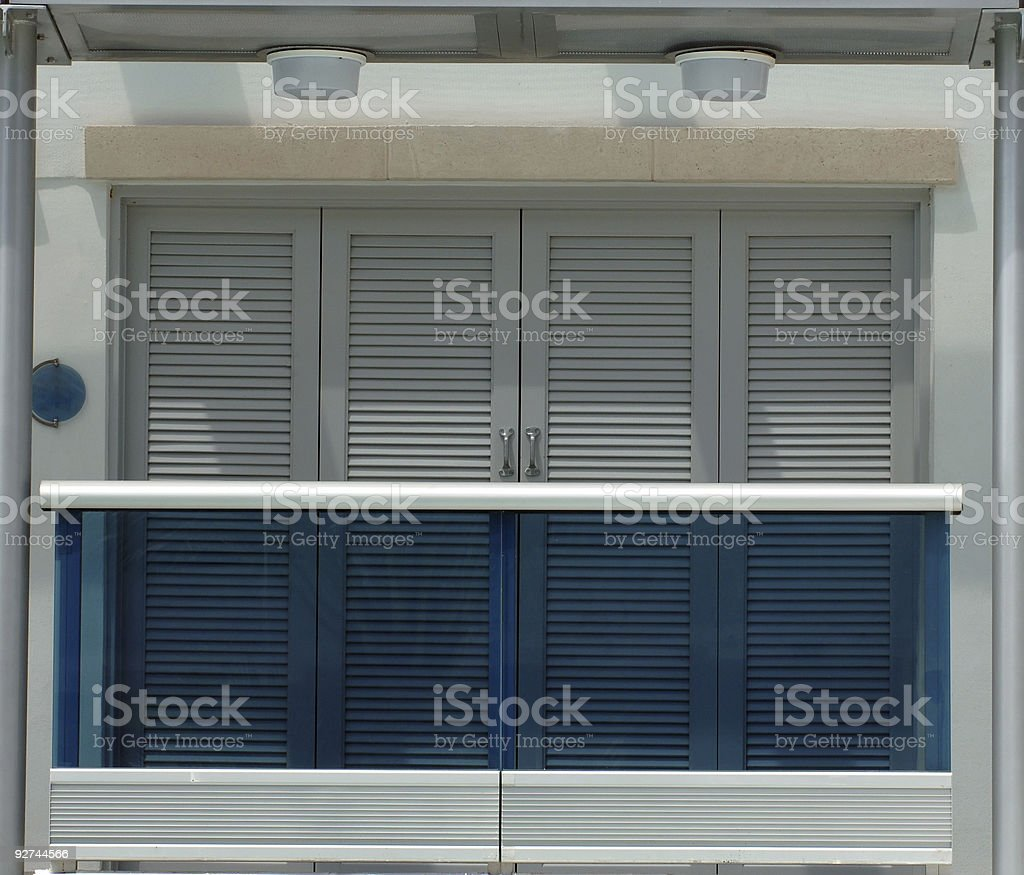 A modern balcony features a glass railing and shutters. royalty-free stock photo
