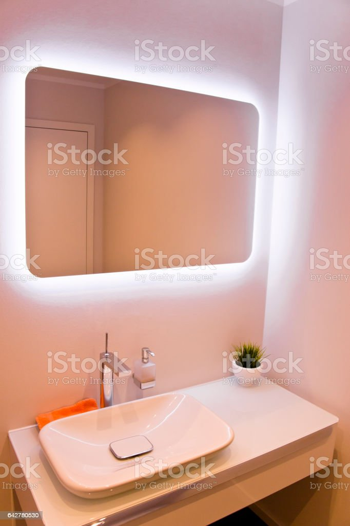 Modern bathroom sink and indirectly lit mirror stock photo