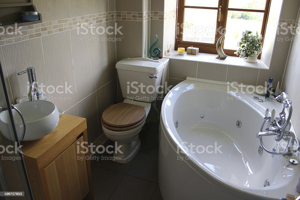 Modern bathroom suite, with toilet, wash basin and corner bath stock photo