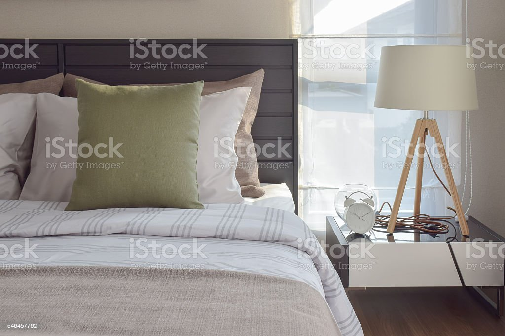 modern bedroom interior with green pillow and decorative lamp stock photo