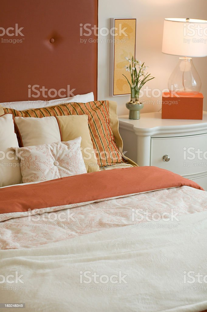 A modern bedroom with an orange and white color scheme royalty-free stock photo