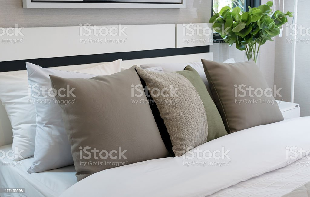 modern bedroom with brown and green pillow on bed stock photo