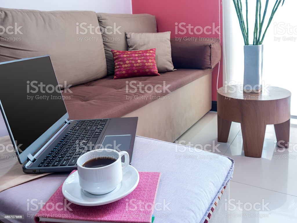 Modern, beige living room with open laptop and coffee cup stock photo