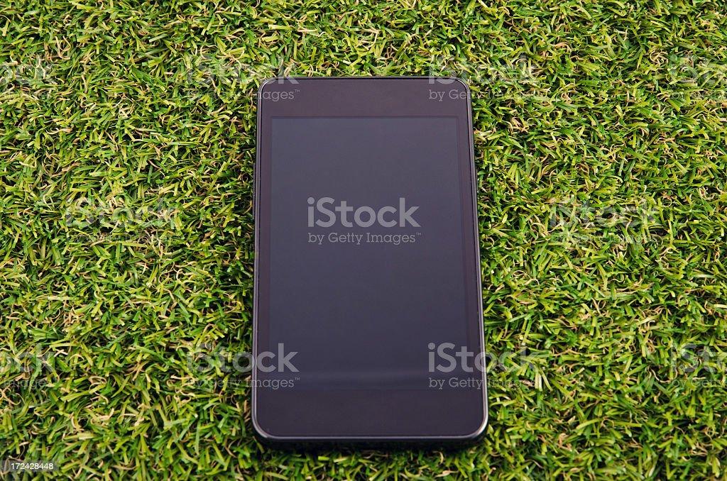Modern black mobile phone on grass stock photo