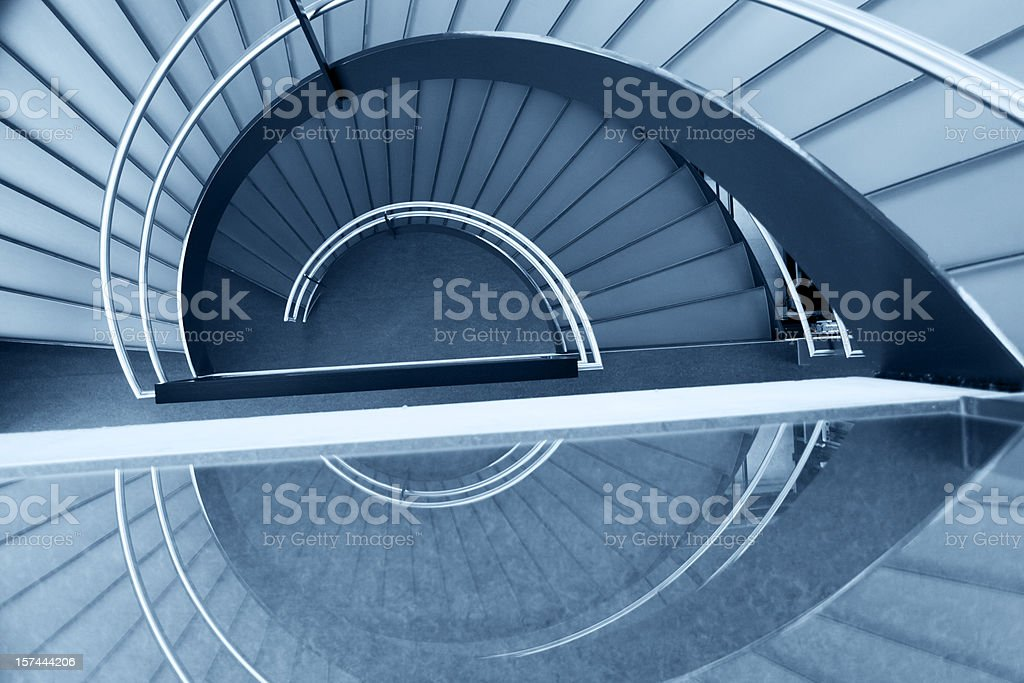 Modern blue spiral staircase and its reflection stock photo
