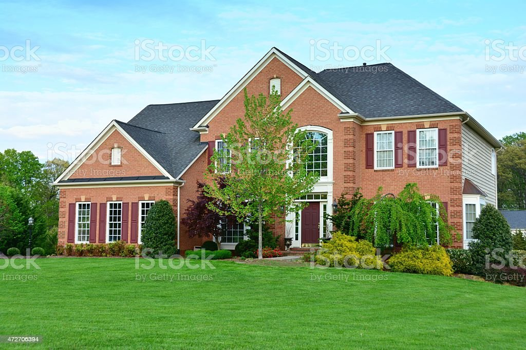 Modern Brick Home with landscaping and green grass stock photo