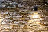 Modern brick, natural stone wall with moden lamp