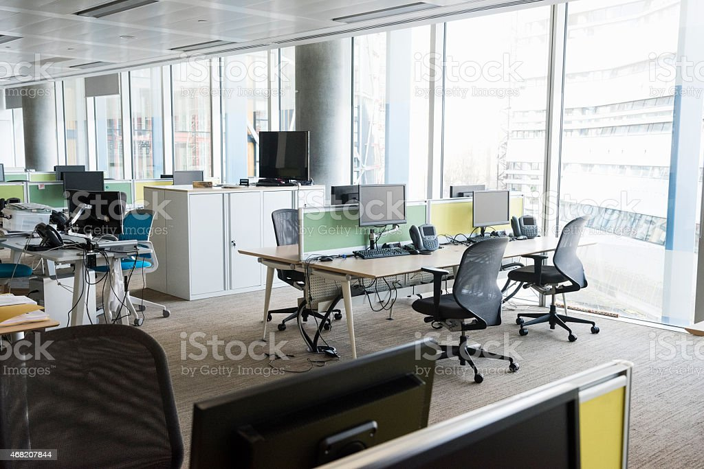 Modern brightly lit office with desks and chairs stock photo