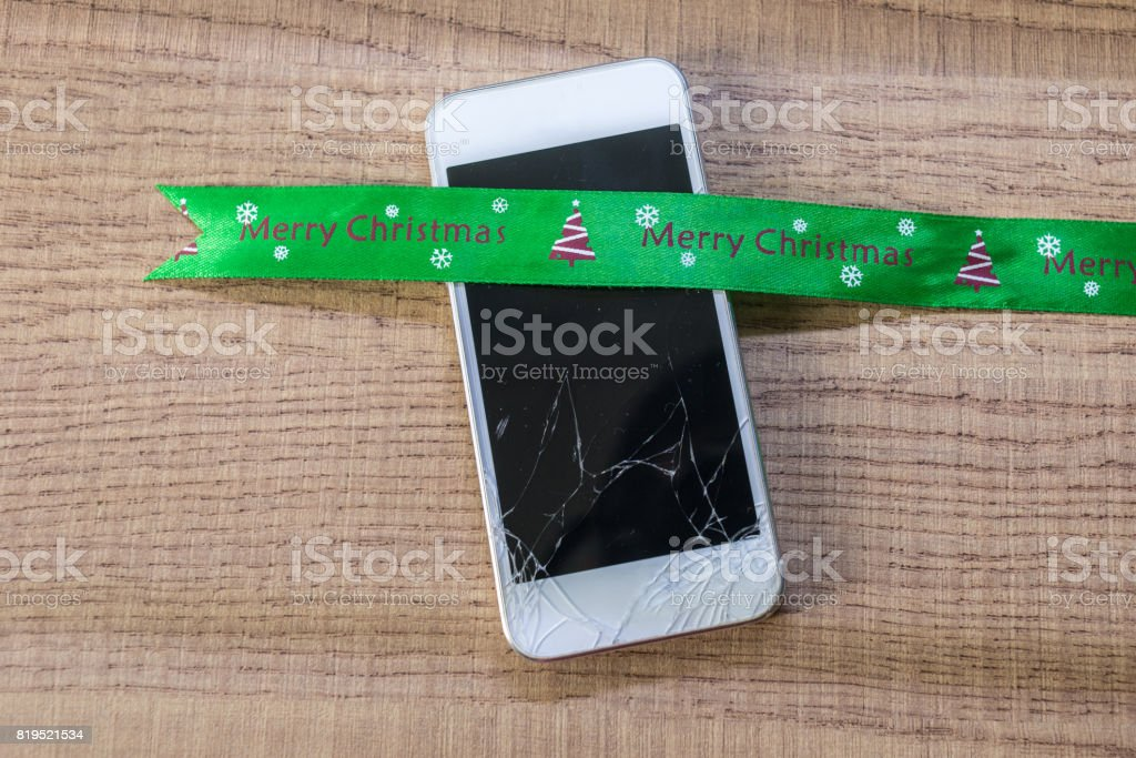 Modern broken mobile phone with the Merry Christmas stock photo