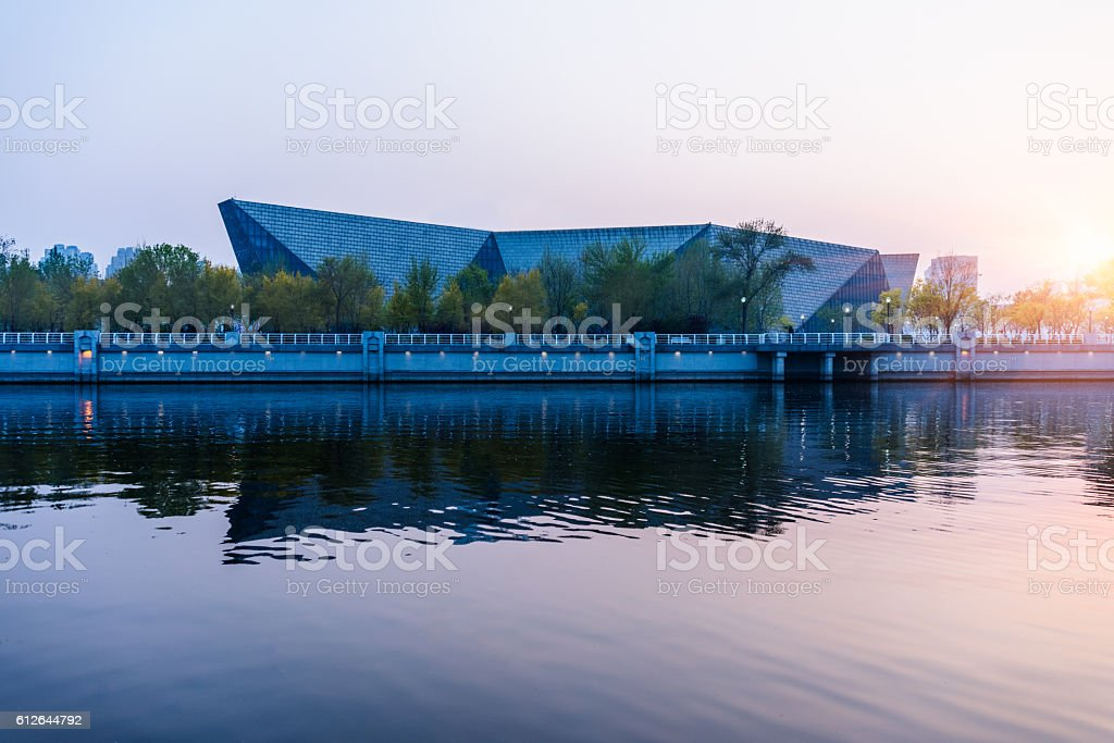 modern building along river at sunset stock photo
