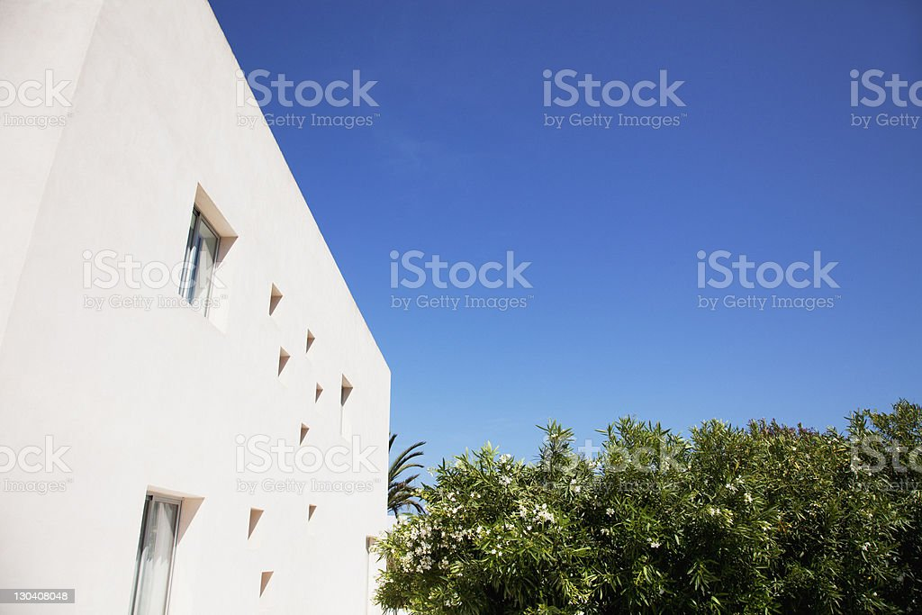 Modern building and trees against blue sky royalty-free stock photo