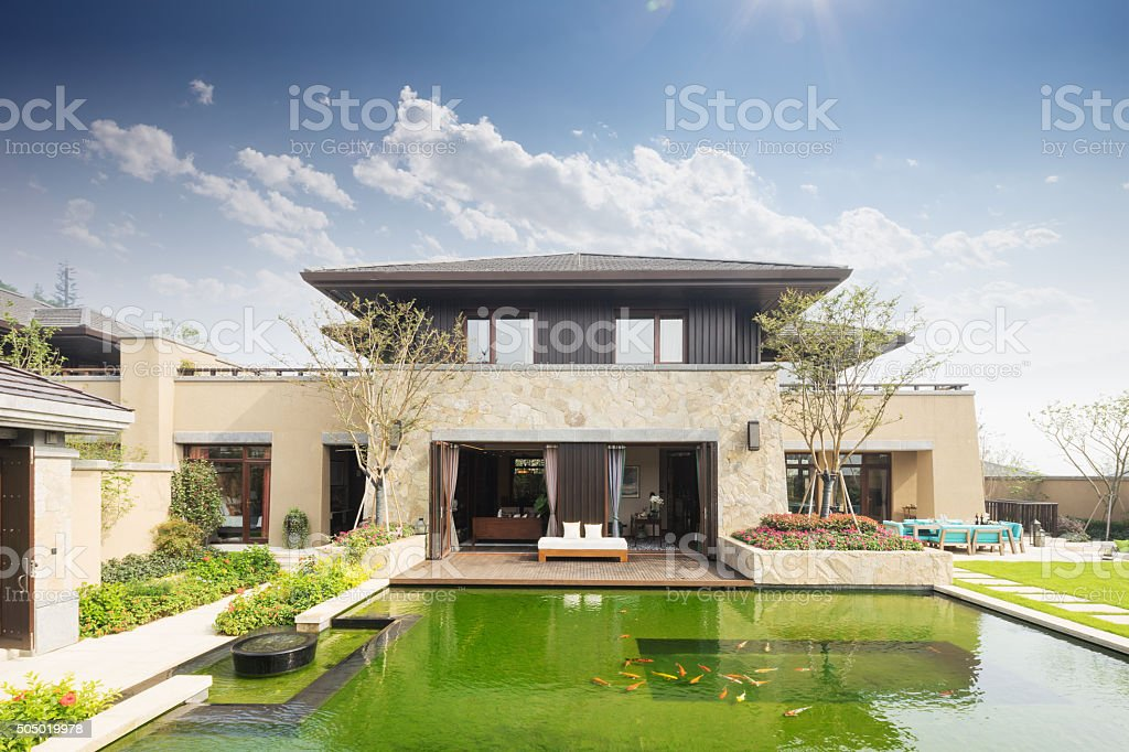modern building near fishpond in blue sky stock photo