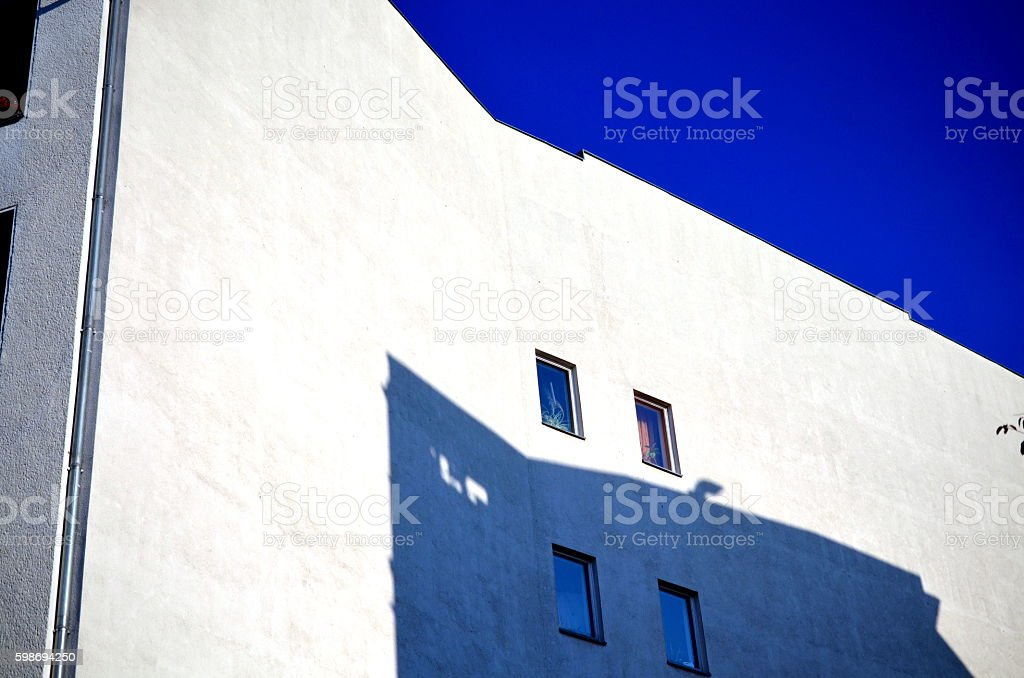 modern building wall with four windows and shadows stock photo