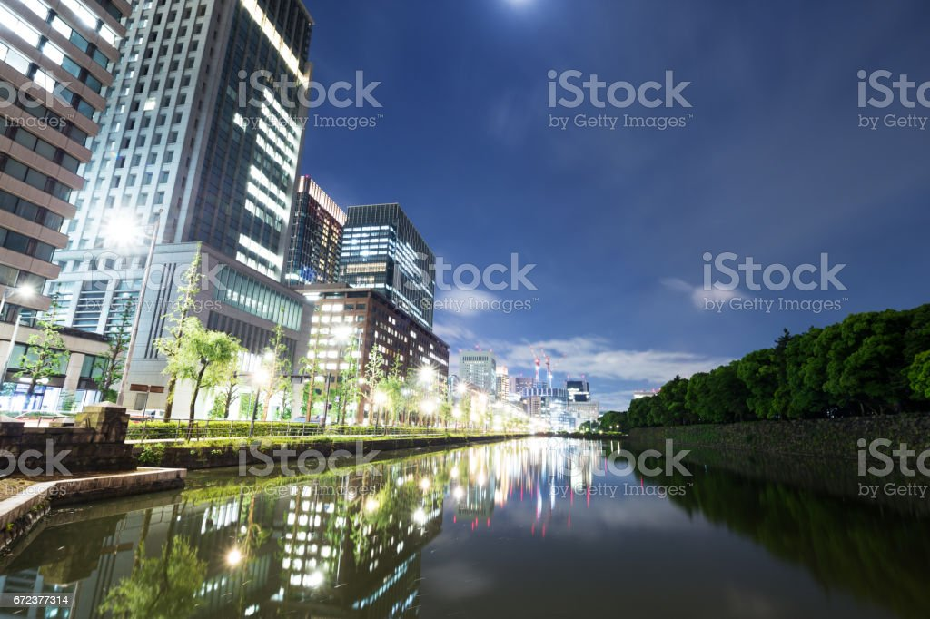 modern buildings by river at twilight stock photo