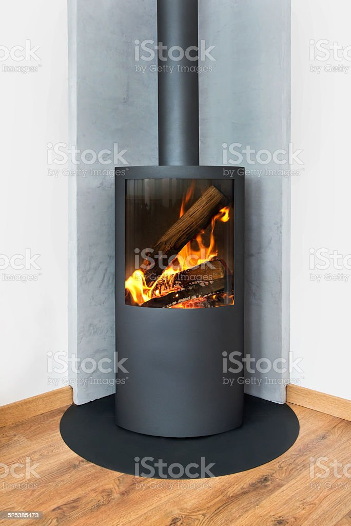 Modern burning stove in a corner of room stock photo