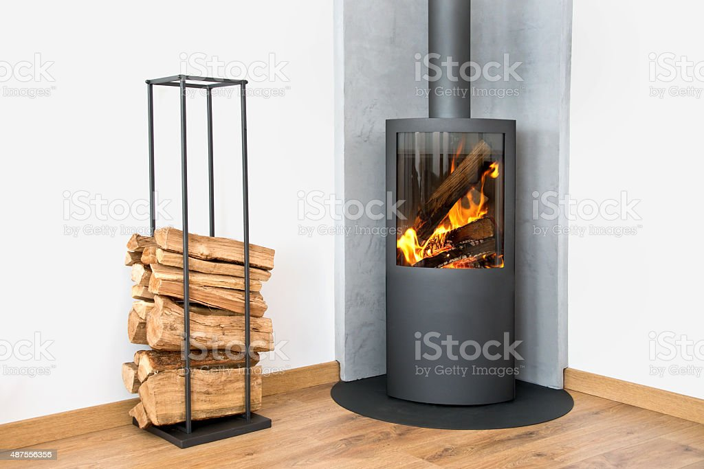 Modern burning stove next to a wood logs rack stock photo