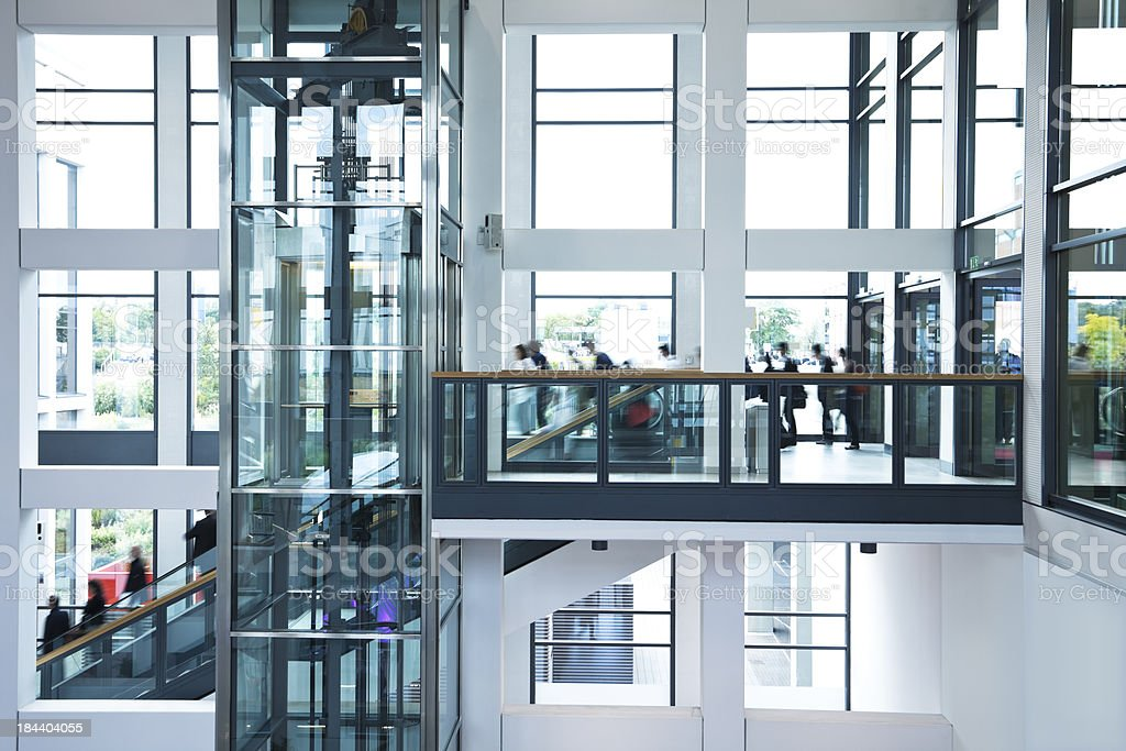 Modern Business Hall with Blurred People, Stairs, Escalators and Elevator stock photo