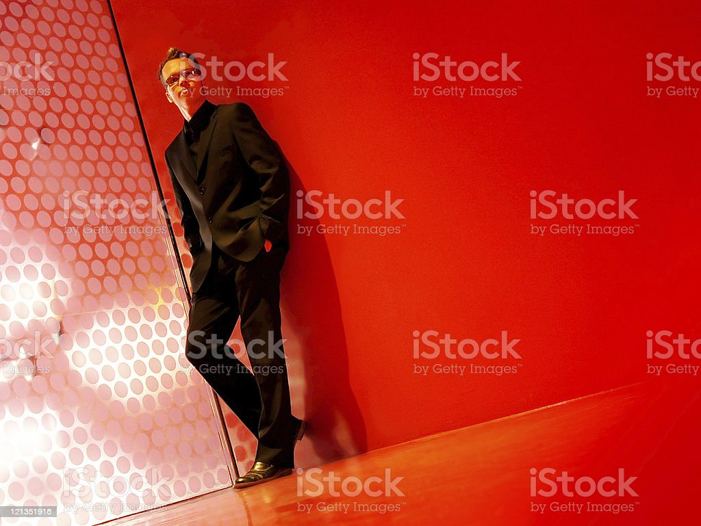 Modern business man in a black suit and red room. royalty-free stock photo