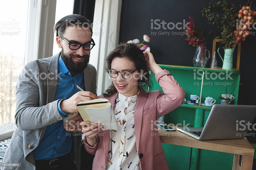 Modern businessman in glasses discussing work with colleague ove stock photo