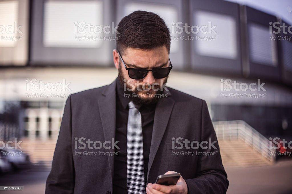 Modern businessman using smart phone outdoors stock photo