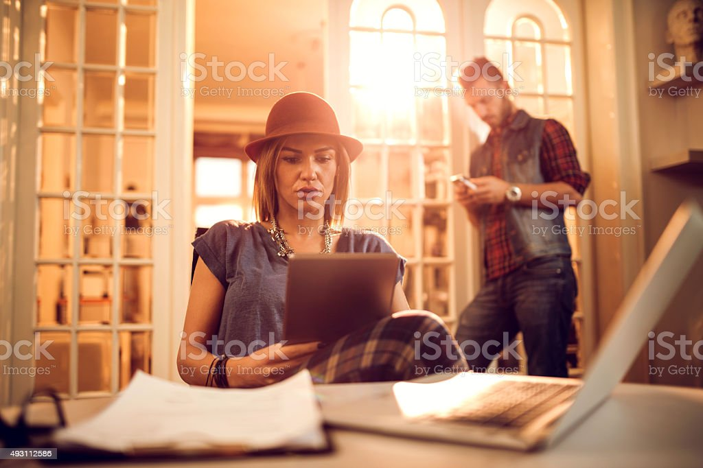 Modern businesswoman reading something on e-reader in the office. stock photo