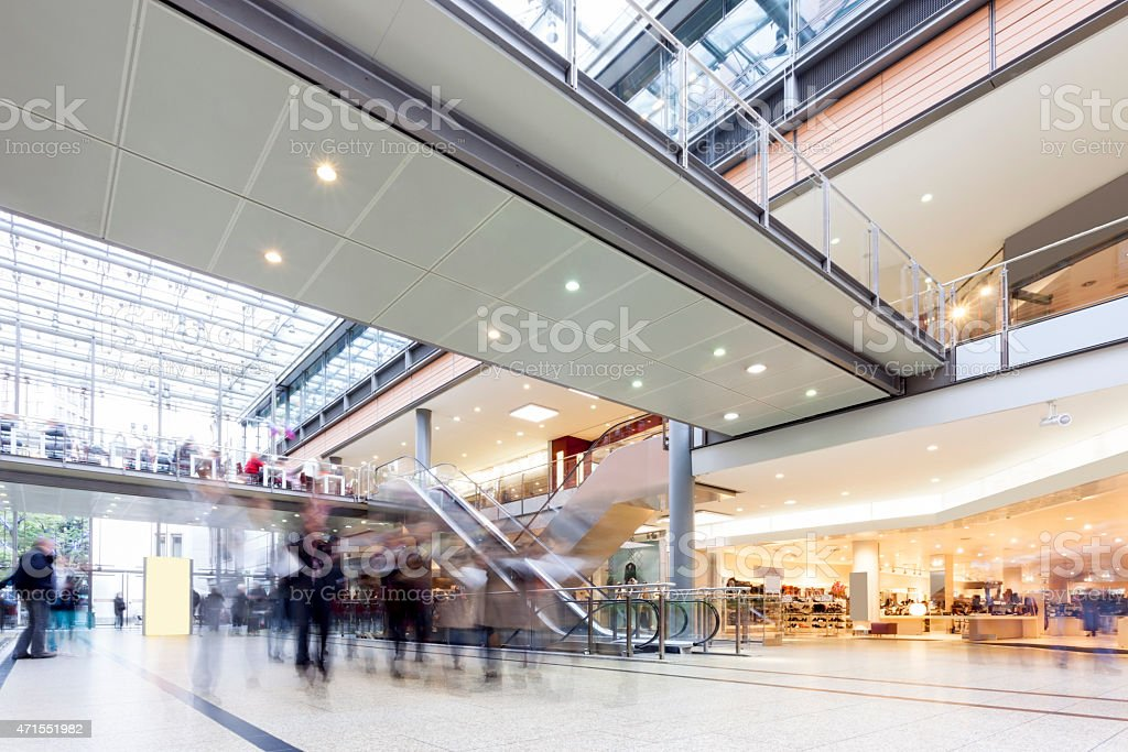 Modern Busy Shopping Mall with motion Blurred Shoppers stock photo