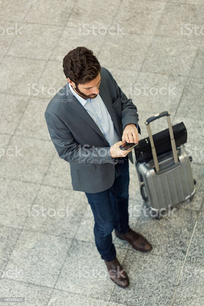 Modern casual business man using cell phone in airport hall stock photo