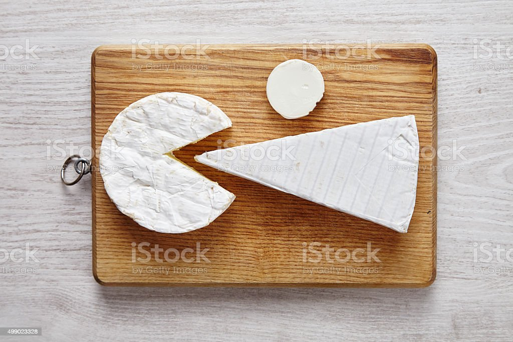 Modern cheese art on chopping plate on white wooden table stock photo