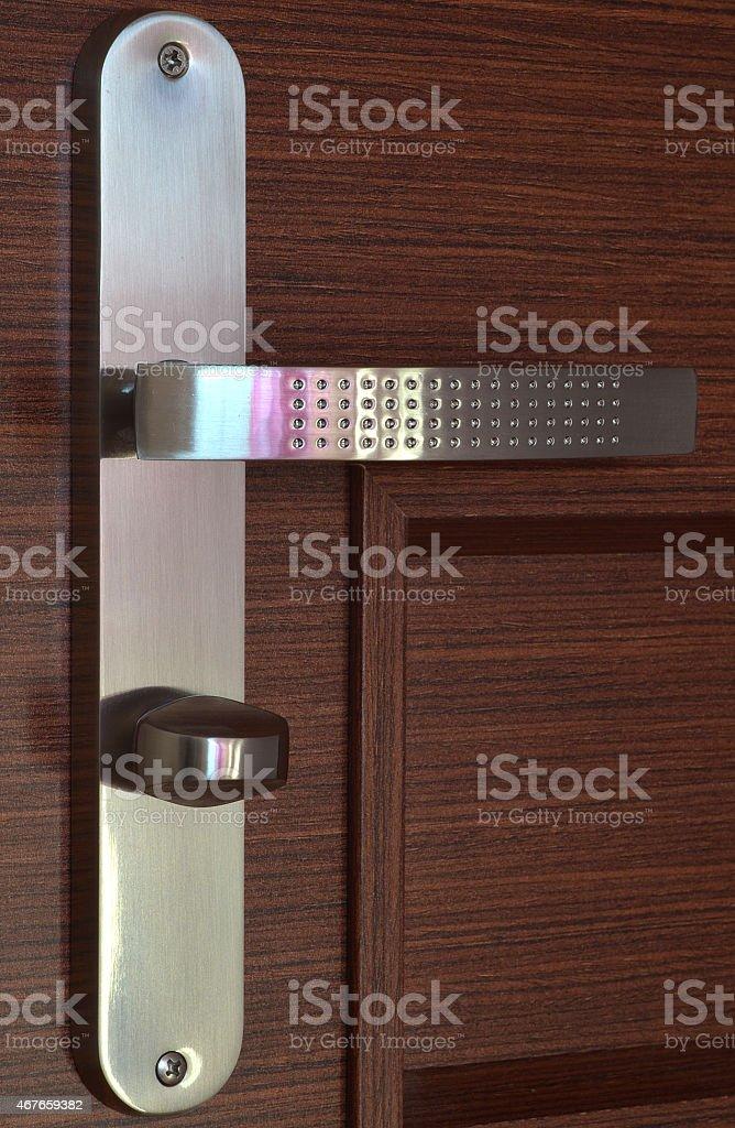 Modern chrome handle on dark brown wooden door stock photo