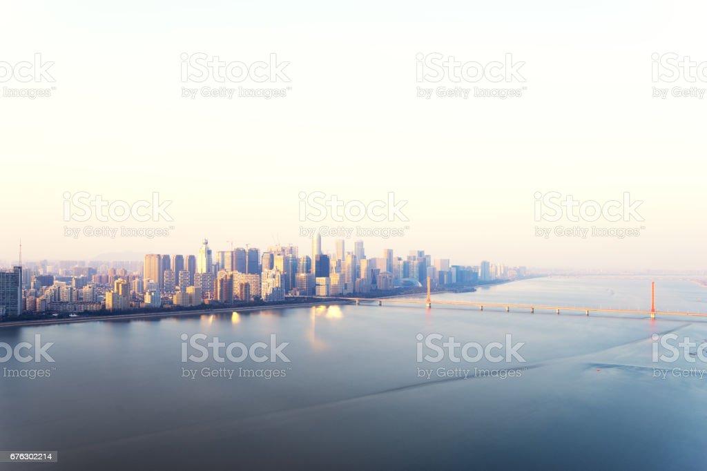 modern city near river at sunrise stock photo
