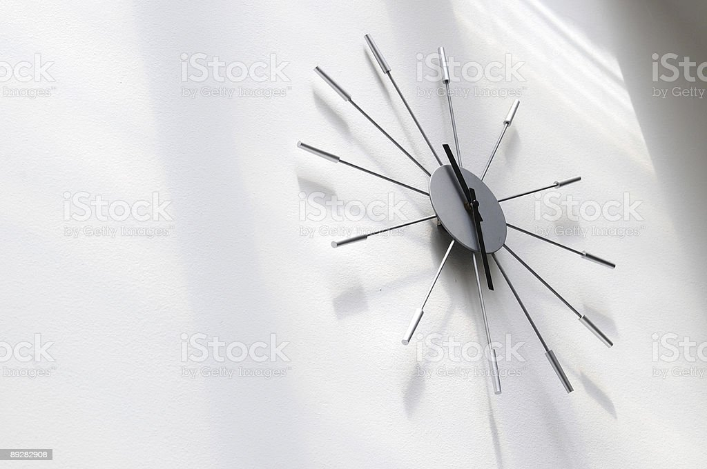 A modern clock, seen from below, on a white wall stock photo