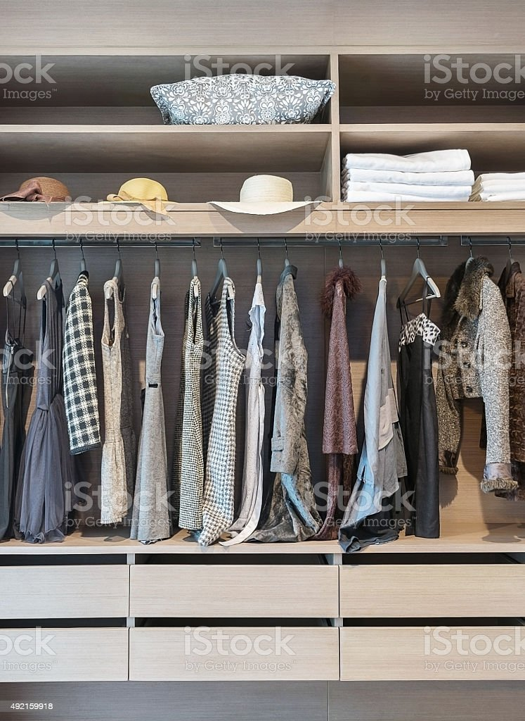 modern closet with row of dress hanging in wardrobe stock photo