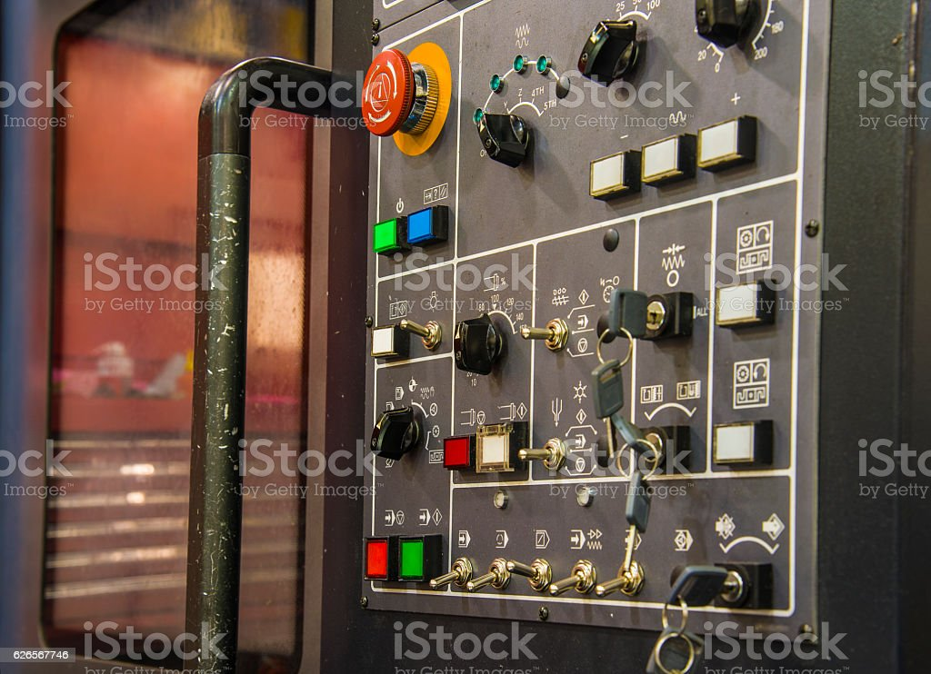 Modern CNC machining center with control panel on foreground. stock photo