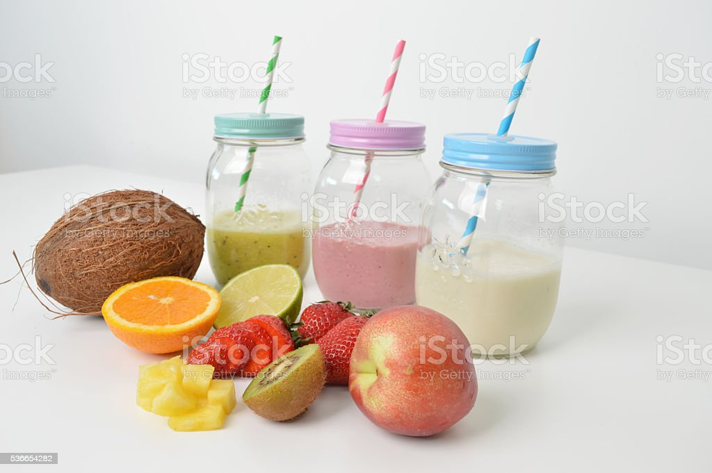 Modern colorfull smoothie jars with a straws and fruits stock photo