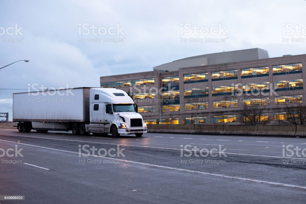 Modern comfort powerful semi truck with dry van trailer delivering industrial cargo on evening road. stock photo