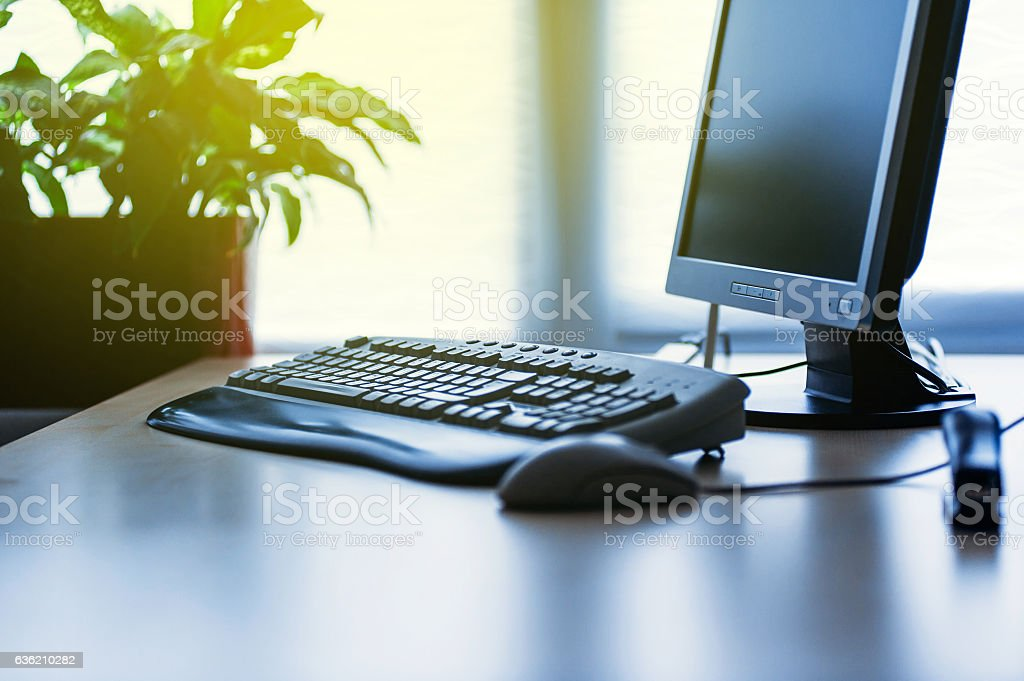 Modern Computer on desk in office lit by sun stock photo