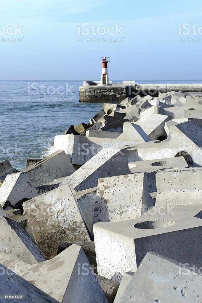 Modern concrete waterbreak and lighthouse at harbour entrance royalty-free stock photo