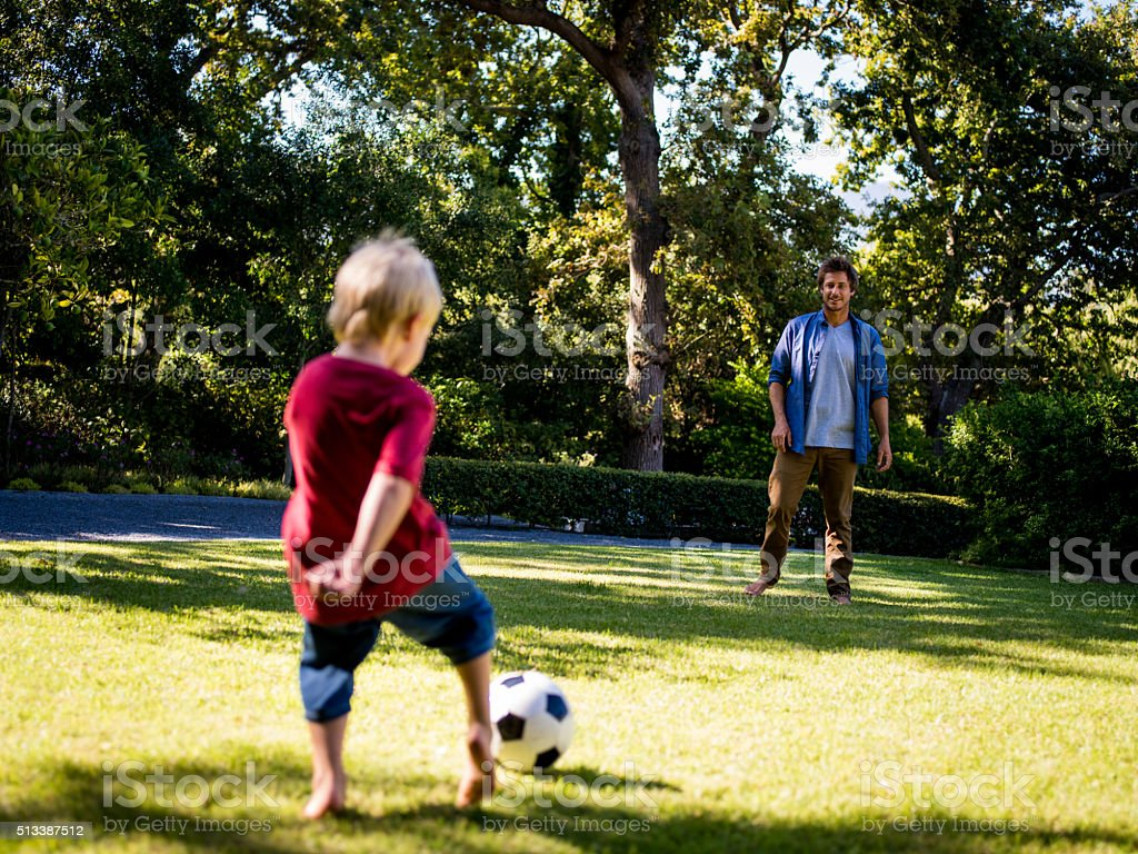 Modern Dad and Little Boy Playing Ball, Barefoot, in Garden stock photo