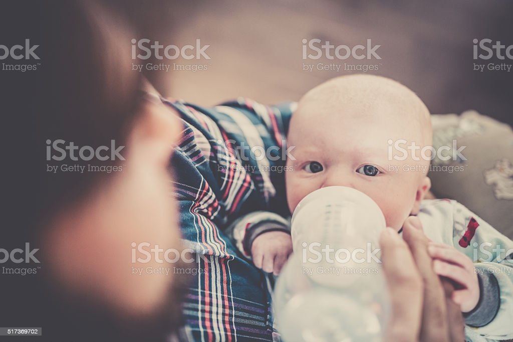 Modern Dad Feeding his Baby Boy with Bottle stock photo