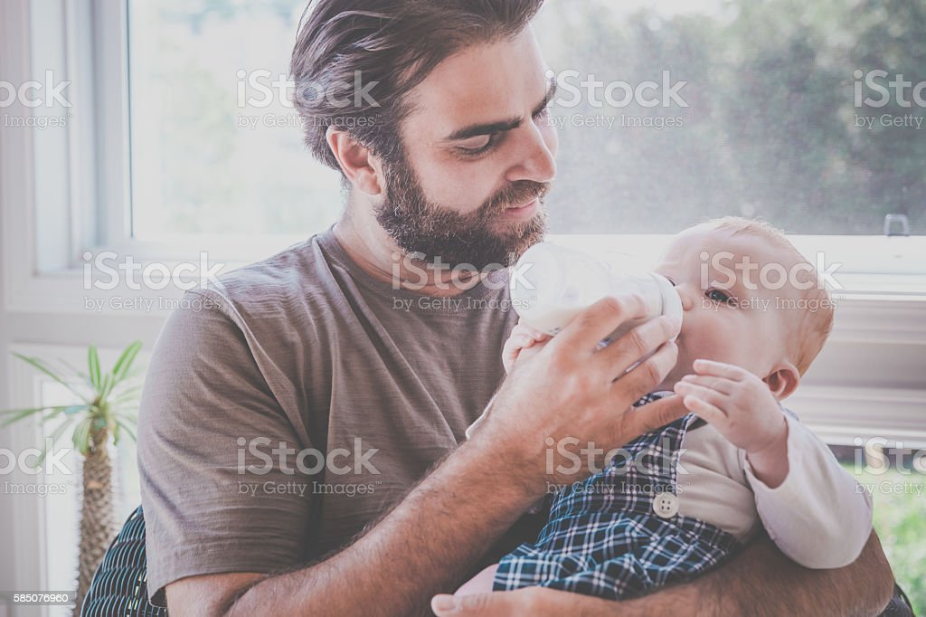Modern Dad Feeding his Baby Boy with Milk Bottle stock photo