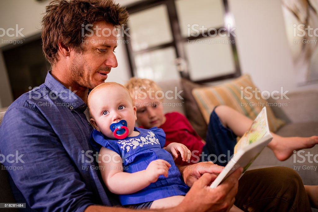 Modern Dad Reading a Book to His Children on Couch stock photo