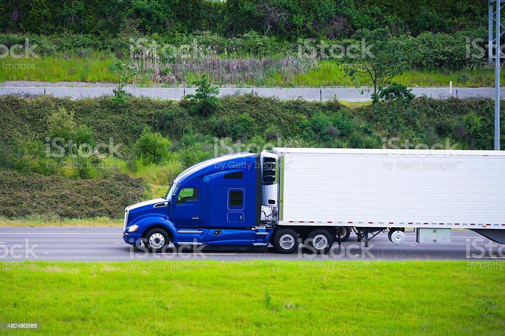 Modern dark blue semi truck reefer trailer profile on road stock photo