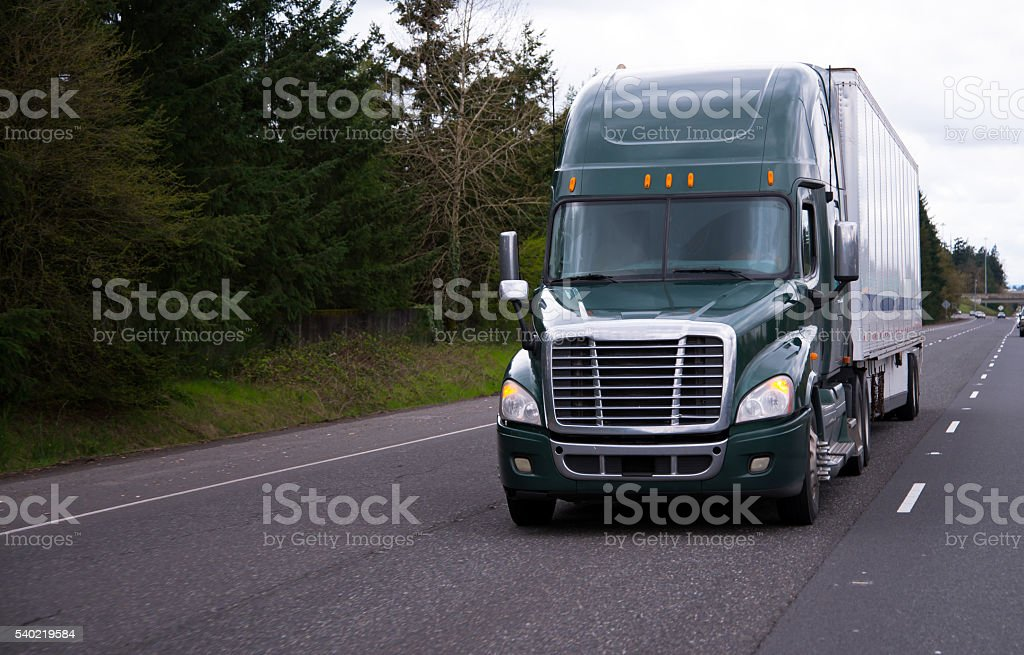 Modern dark green semi truck and trailer on straight road stock photo
