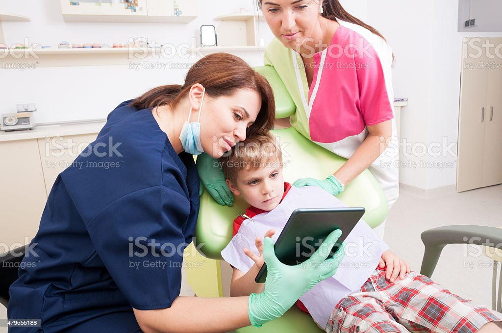 Modern dental team entertaining kid or child patient stock photo
