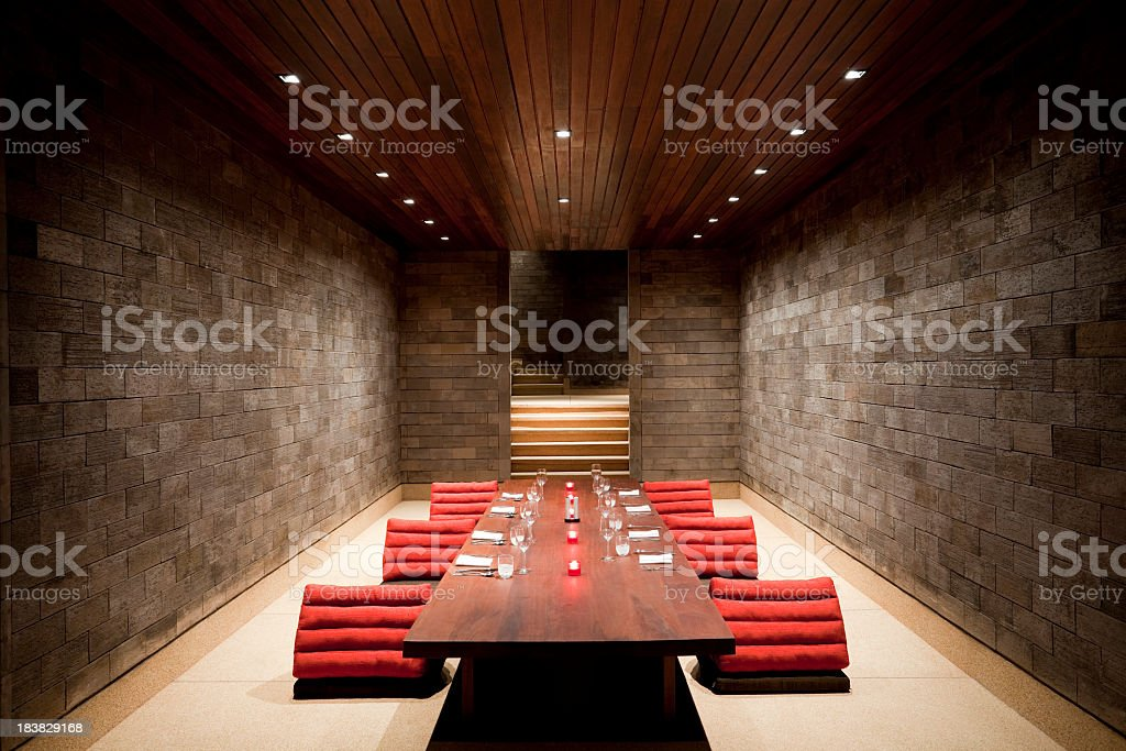 Modern dining room table with red stools in rich stone villa stock photo